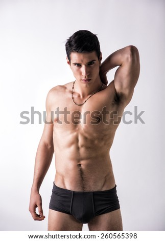 Handsome, fit young man wearing only underwear standing on white background, looking at camera - stock photo