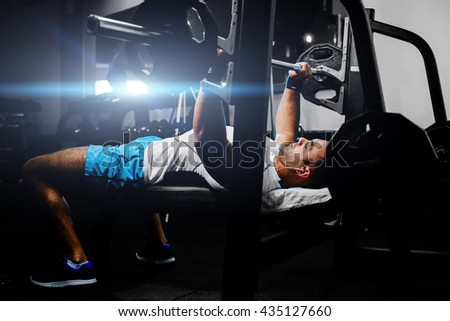 handsome fitness man weightlifting in gym with happy face - stock photo