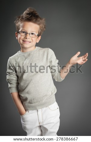 Handsome five year old boy posing in studio over gray background. Boy wearing reading glasses.