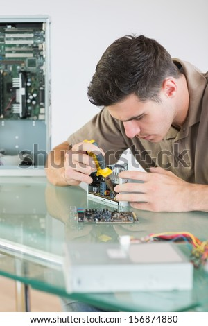 Handsome focused computer engineer repairing hardware with pliers in bright office