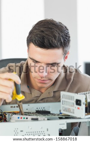 Handsome focused computer engineer repairing open computer in bright office - stock photo