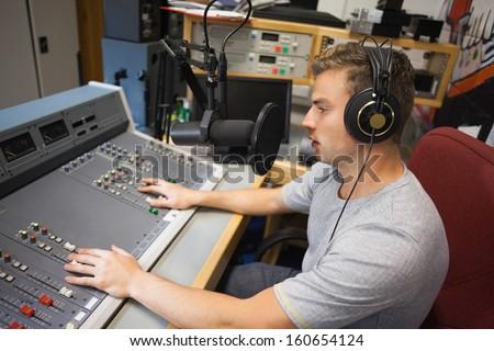 Handsome focused radio host moderating in studio at college - stock photo