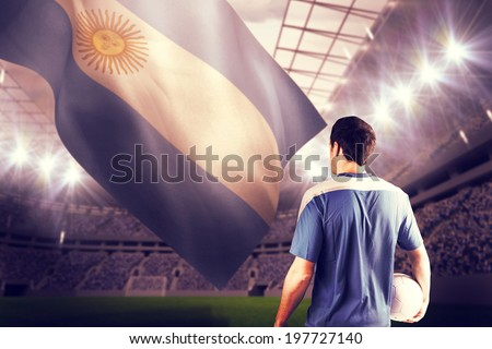 Handsome football player holding the ball against football stadium - stock photo
