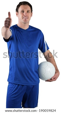 Handsome football player holding the ball on white background