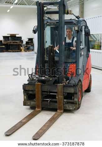 Handsome forklift operator working in the warehouse. - stock photo