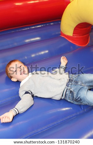handsome funny little boy playing on the playground - stock photo