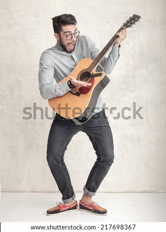 handsome funny man playing an acoustic guitar against grunge wall