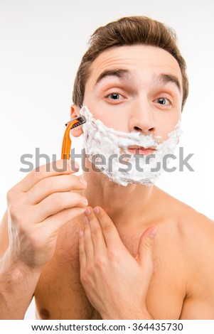 Handsome funny man with shaving foam on his face and razor