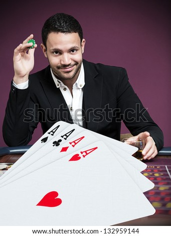Handsome gambler betting on four aces in foreground - stock photo