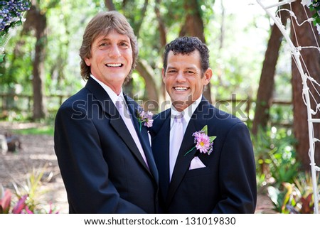 Handsome gay couple getting married under a floral archway, in outdoor ceremony. - stock photo