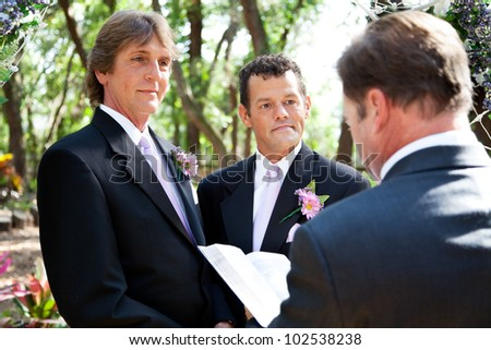 Handsome gay male couple getting married by a minister in beautiful outdoor setting. - stock photo