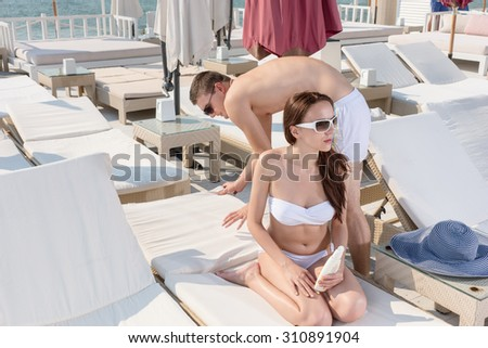 Handsome Gentleman Fixing the Lounge Chair of his Pretty Girlfriend While Having a Vacation in the Resort. - stock photo