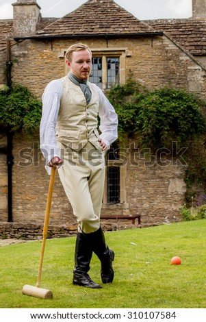 Handsome ginger hair man dressed in regency period costume playing croquet. Image with selective focus - stock photo