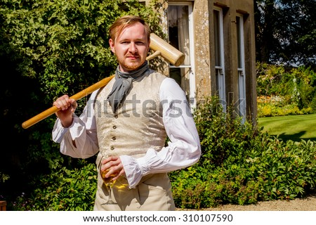 Handsome ginger hair man dressed in regency period costume with glass of sparkling vine and croquet mallet. Image with selective focus - stock photo