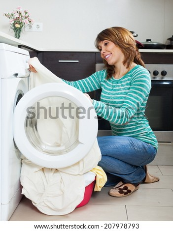 Handsome girl in green using washing machine at home