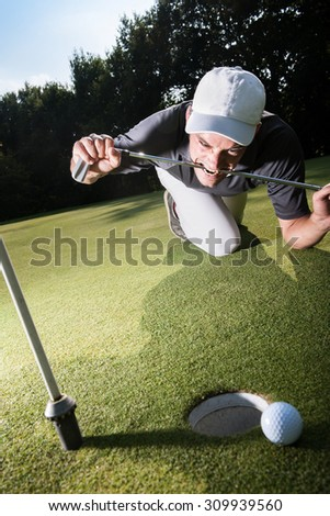 Handsome golfer lying down on the green, hands on the ground, biting his club because he missed his shot. Wide angle view with the flag pole on the foreground and a beautiful forest in the background - stock photo