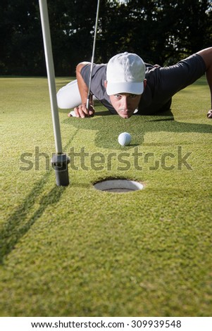 Handsome golfer lying down on the green, hands on the ground, checking the line of putt of his ball. Wide angle view with the flag pole on the foreground and a beautiful forest in the background - stock photo