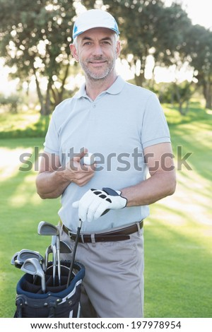 Handsome golfer standing with golf bag on a sunny day at the golf course - stock photo