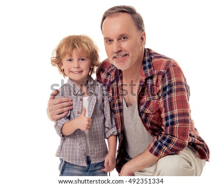 Handsome grandpa and grandson are looking at camera and smiling, isolated on white. Little boy is showing Ok sign
