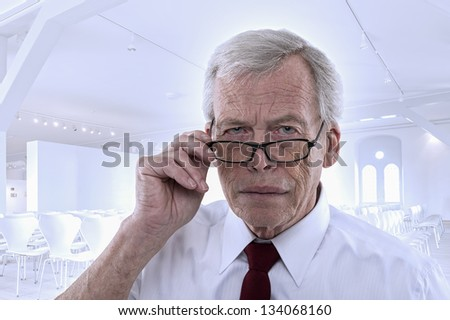 Handsome grey haired senior business man lowering his glasses and peering at the camera with a serious expression against a high key architectural background - stock photo