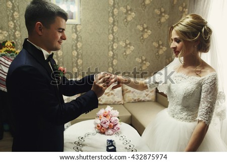 handsome groom and beautiful blonde bride exchanging golden wedding rings - stock photo