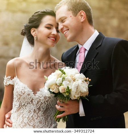Handsome groom and beautiful sexual brunette bride hugging in garden old wall background