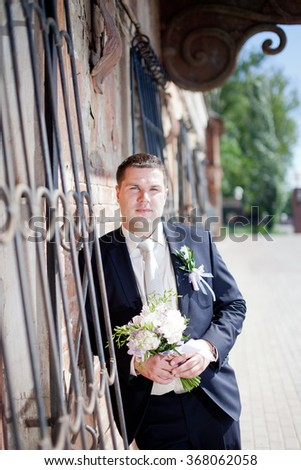 Handsome groom at wedding tuxedo smiling and waiting for bride