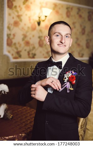 Handsome groom at wedding tuxedo smiling and waiting for bride  in a luxurious restaurant. Happy smiling groom newlywed. Rich groom at wedding day. Handsome caucasian man in tuxedo.