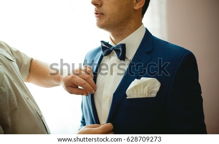 Handsome groom getting dressed and preparing for the wedding