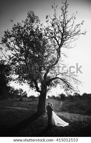 Handsome groom hugging blonde bride in forest at sunset b&w