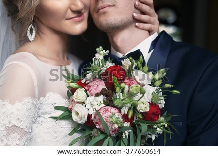 Handsome groom hugging happy bride in french street closeup - stock photo