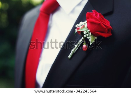 Handsome groom in black suit and red tie with red rose boutonniere closeup