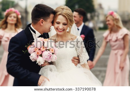 Handsome groom in suit hugging elegant blonde bride with bridesmaids and groomsmen - stock photo