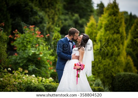 Handsome groom kissing beautiful bride with bouquet in romantic european park - stock photo