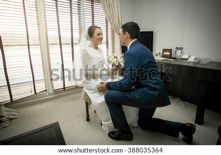 Handsome groom kneeling in front of bride sitting at hotel room