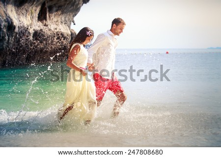 handsome groom run with his beautiful brunette bride in long white wedding dress on island bay with green mountain background in Thailand - stock photo