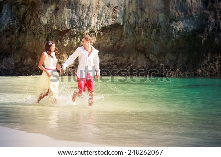 handsome groom run with his beautiful brunette bride in long white wedding dress on island bay with green mountain background in Thailand