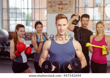 Handsome group of five fit young people in room holding kettle bell, dumb bell, resistance bands and boxing gloves - stock photo