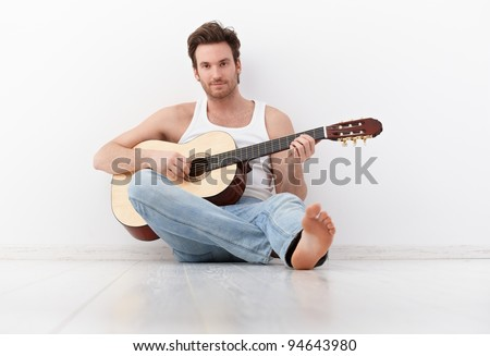 Handsome guitar player sitting on floor, practicing.?
