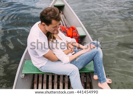 handsome guy and beautiful girl resting in a boat on the lake - stock photo