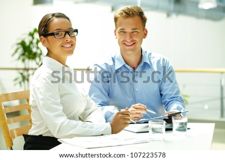 Handsome guy and his pretty colleague looking at camera while solving some business matters - stock photo