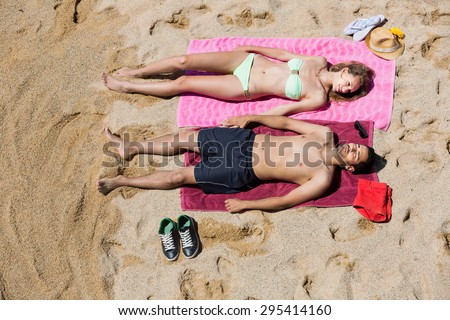 Handsome guy and pretty girlfriend resting on sand at sea beach