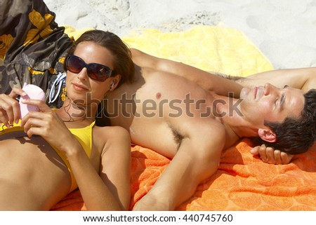 Handsome guy and pretty girlfriend resting on sand at sea beach - stock photo