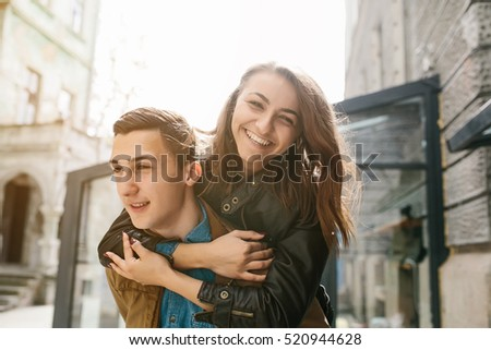 handsome guy carries a pretty girl on his back