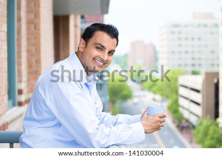 Handsome guy enjoying his drink on a balcony, isolated on a city background - stock photo