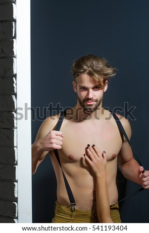 Handsome guy fashion sexy young bearded macho man model with suspenders on pants with female hand on bare muscular torso holds on brick wall and grey background
