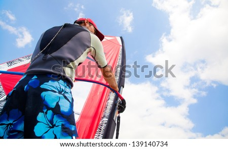 handsome guy holding on to sail windsurfing riding in the sea
