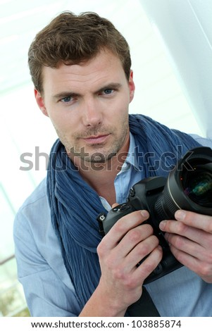 Handsome guy holding photo camera - stock photo