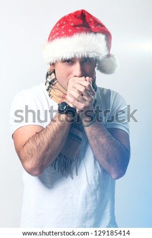 Handsome guy in christmas hat feels cold - stock photo