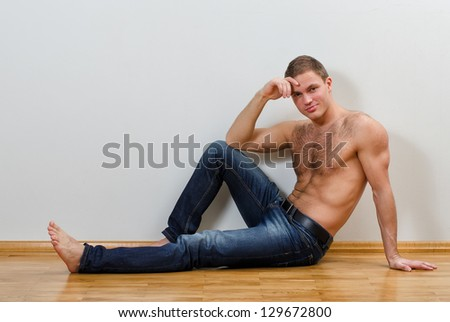 Handsome guy in jeans with bare torso sitting on the floor near the wall - stock photo